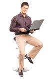Un uomo sorridente che sitiing su un seggiolone e che lavora ad un computer portatile Fotografia Stock Libera da Diritti