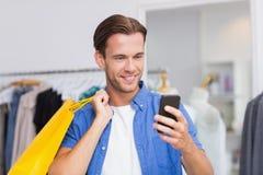 Un uomo sorridente con i sacchetti della spesa che esaminano il suo smartphone Immagini Stock