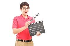Un uomo sorridente con i vetri che tengono un applauso di film Fotografia Stock
