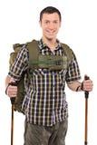 Un uomo sorridente con lo zaino ed i pali di escursione Immagini Stock Libere da Diritti