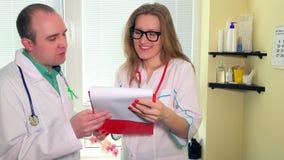 Un uomo sorridente e una donna di due medici che discutono esaminando la cassa paziente della cartella archivi video