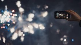 Un uomo spara un video del selfie di una manifestazione pirotecnica festiva in una città di notte Fotografia Stock