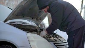 Un uomo spegne la batteria della sua automobile È esterno molto freddo stock footage