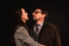 Un uomo sta abbracciando una ragazza contro un fondo scuro fotografia stock libera da diritti