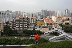 Un uomo sta al bordo di una cima del tetto in Canton Fotografia Stock