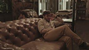 Un uomo sta aspettando una donna e sta avvertendo la seduta sul sofà video d archivio