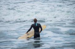 Un uomo sta camminando con una spuma in sue mani attraverso la riva di mare Fotografie Stock