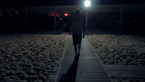 Un uomo sta camminando da solo nello scuro sulle vie archivi video