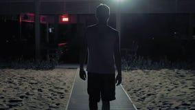 Un uomo sta camminando da solo nello scuro sulle vie stock footage