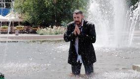Un uomo sta camminando in una fontana, sta coprendo il suo fronte di mani e sta ritenendo tutta la tristezza nel mondo video d archivio