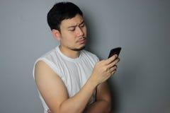 Un uomo sta considerando il telefono cellulare immagini stock