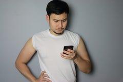 Un uomo sta considerando il telefono cellulare fotografia stock libera da diritti