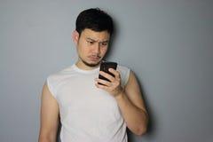 Un uomo sta considerando il telefono cellulare fotografie stock
