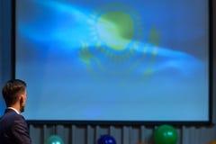 Un uomo sta esaminando un grande schermo con un'immagine del sole e di un'aquila su un fondo blu Simboli del Kazakistan immagine stock