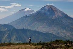 Un uomo sta esaminante la bellezza delle montagne di Sumbing e di Sindoro fotografie stock
