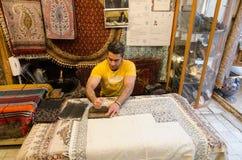 Un uomo sta facendo la stampa persiana Fotografie Stock Libere da Diritti