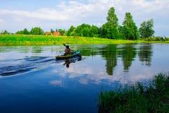 Un uomo sta galleggiando su un kajak nave Fotografia Stock