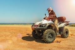 Un uomo sta guidando ATV su fuori strada Fotografie Stock