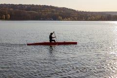 Un uomo sta guidando un kajak fotografia stock