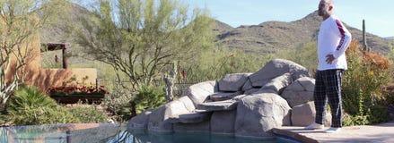 Un uomo sta il Poolside nel deserto del ` la s Sonoran dell'Arizona Fotografia Stock Libera da Diritti