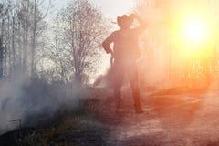 Un uomo sta indossando un cappello da cowboy e un loso nel campo americano Fotografia Stock