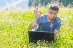 Un uomo sta lavorando ad un computer portatile in natura e mostra un'approvazione del segno, libera Immagini Stock