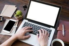 Un uomo sta lavorando usando un computer portatile sulla tavola di legno d'annata Fotografie Stock