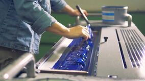 Un uomo sta livellando la pittura blu in un vassoio di stampatrice stock footage