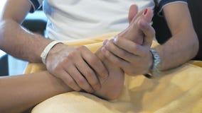 Un uomo sta massaggiando qualcuno piede archivi video