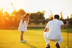 Un uomo sta occupando su un club di golf e sta esaminando una ragazza che sta oscillando un club per colpire la palla Immagini Stock