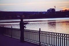 Un uomo sta pescando per la sera nel lago immagine stock libera da diritti