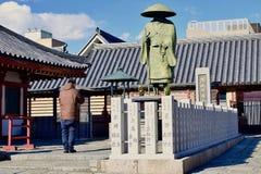 Un uomo sta pregando al tempio del Giappone Osaka Shitennoji in un giorno soleggiato fotografia stock libera da diritti