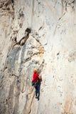 Un uomo sta preparandosi per scalare su una roccia Fotografia Stock Libera da Diritti