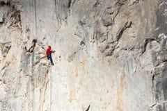 Un uomo sta preparandosi per scalare su una roccia Fotografie Stock