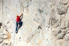 Un uomo sta preparandosi per scalare su una roccia Immagine Stock
