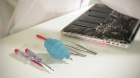 Un uomo sta riparando un computer portatile Il concetto della riparazione del computer Chiuda su della scheda madre del computer  video d archivio
