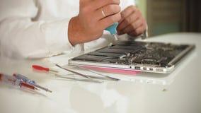Un uomo sta riparando un computer portatile Il concetto della riparazione del computer Chiuda su della scheda madre del computer  stock footage