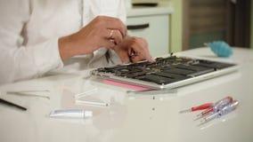 Un uomo sta riparando un computer portatile Il concetto della riparazione del computer Chiuda su della scheda madre del computer  archivi video