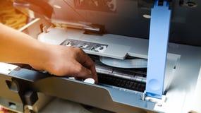 Un uomo sta riparando una stampante macchina digitale della fotocopiatrice apparecchiature di stampa, analizzatore 3d fotografia stock