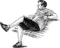 Un uomo sta riposando su un banco di parco Immagini Stock
