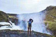Un uomo sta sull'orlo di una cascata fotografie stock libere da diritti