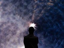 Un uomo sta in un tunnel con luce all'estremità fotografia stock libera da diritti