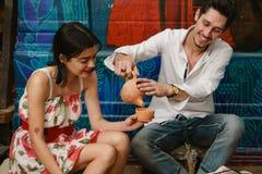 Un uomo sta versando il tè nella tazza di una ragazza Fotografia Stock Libera da Diritti