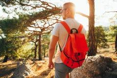 Un uomo sta viaggiando con uno zaino leggero nelle montagne Immagine Stock Libera da Diritti