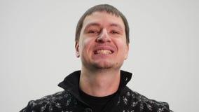 Un uomo su un fondo bianco sorride e ride nella macchina fotografica video d archivio