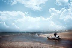 Un uomo su un'imbarcazione a motore naviga dalla riva al mare aperto immagini stock