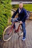 Un uomo su una retro bicicletta in un parco fotografia stock
