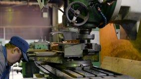 Un uomo sul lavoro su una fresatrice verticale Lavorando di una parte di metallo su una macchina per il taglio di metalli video d archivio