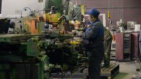 Un uomo sul lavoro su una fresatrice verticale Lavorando di una parte di metallo su una macchina per il taglio di metalli archivi video