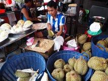 Un uomo taglia i frutti del durian in una via Fotografia Stock